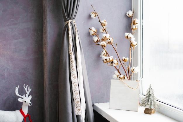 Gałązki bawełny w wazonie przy oknie. świąteczny wystrój w domu. przytulny nowy rok i zima