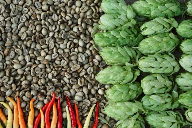 Gałązki chmielu, zielone ziarna kawy, czerwone chili na tle pęknięty drewniany stół. vintage stonowany. składniki piwa.
