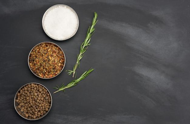 Gałązki rozmarynu, soli i pieprzu w żelaznym talerzu na czarnym tle, widok z góry, miejsce kopiowania