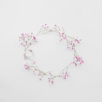 Gałązki świeżych kwiatów skomponowane w okrąg