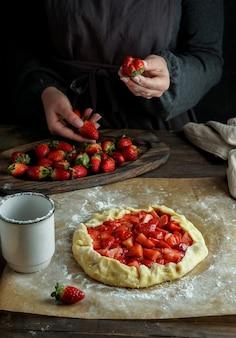 Galette z procesem przygotowania świeżych truskawek, ręce młodej kobiety, praca z ciastem