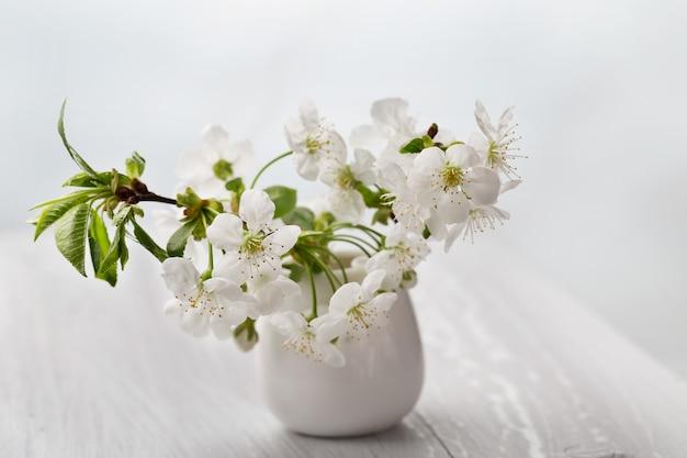 Gałęziasta kwitnie wiśnia w białej wazie na stole