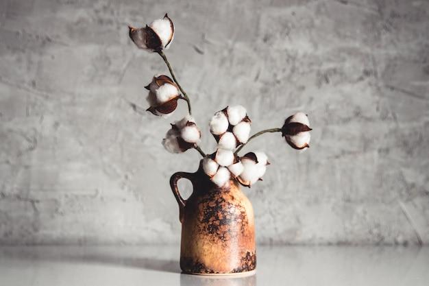 Gałęzie bawełny w brązowym wazonie wiklinowym na tle szaro-niebieskiej ściany