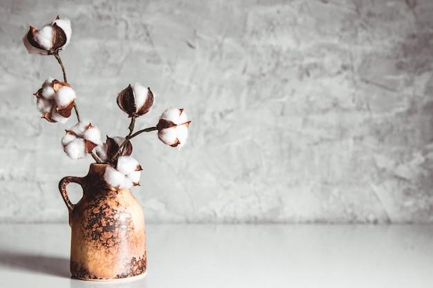 Gałęzie bawełny w brązowym wazonie z wikliny na szaro-niebieskiej ścianie
