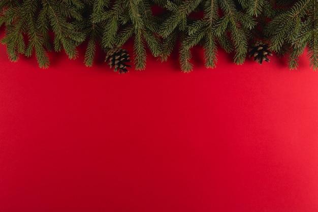 Gałęzie choinki w formie ramki na czerwonym, boże narodzenie, copyspace kartkę z życzeniami.