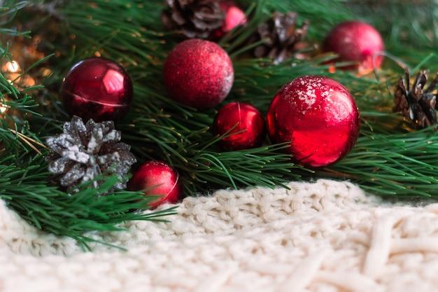 Gałęzie choinki z czerwonymi kulkami i szyszkami na białym swetrze z dzianiny
