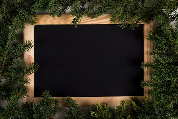 Gałęzie choinkowe i rama czarna deska drewniana, boże narodzenie, kartkę z życzeniami. copyspace.