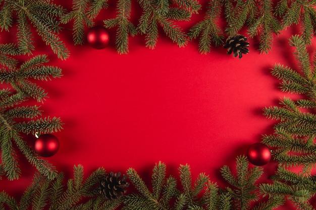 Gałęzie choinkowe i szyszki na czerwonym, boże narodzenie, lato kartkę z życzeniami.