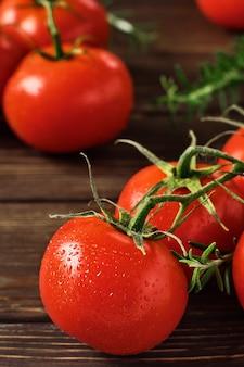 Gałęzie dojrzałych czerwonych pomidorów i gałązek rozmarynu na ciemnym drewnianym stole