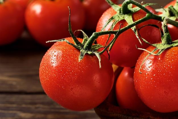 Gałęzie dojrzałych soczystych czerwonych pomidorów na ciemnej drewnianej ścianie. zbliżenie, selektywna ostrość. pomidory w kroplach wody. naturalne świeże jedzenie z rynku do przygotowania najlepszych potraw