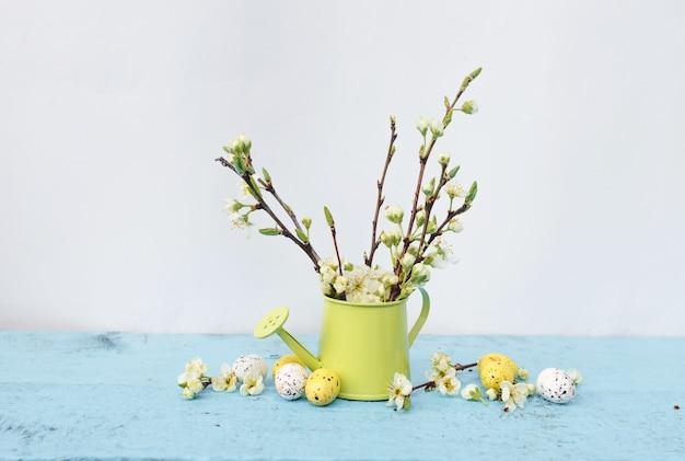 Gałęzie drzewa o białych kwiatach w wazonie jasnozielonego koloru, kolorowe jaja przepiórcze na jasnoniebieskim tle. wiosenna piosenka wielkanocna.
