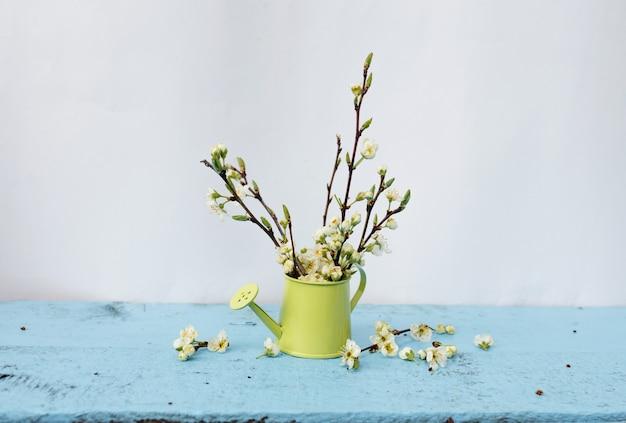 Gałęzie drzewa o białych kwiatach w wazonie o jasnozielonym kolorze na jasnoniebieskim tle. wiosenna kompozycja kwiatowa