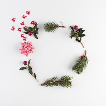 Gałęzie iglaste, kwiaty i łuk
