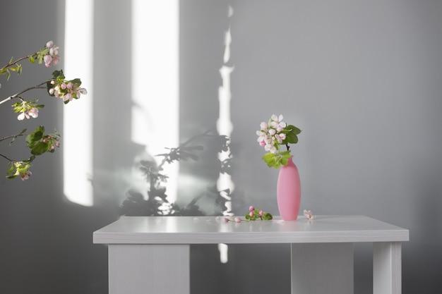 Gałęzie jabłoni z kwiatami w różowym wazonie na białym stole