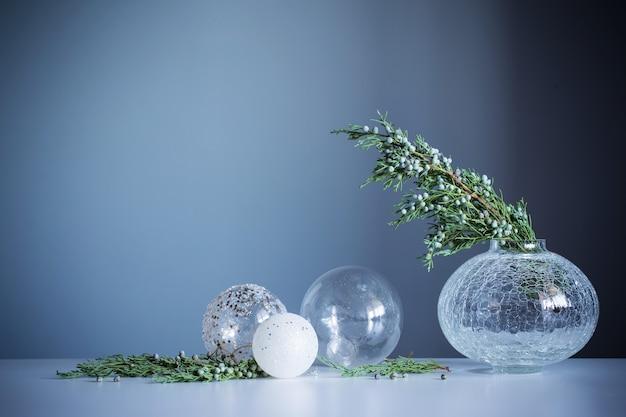Gałęzie jałowca w szklanym wazonie i bombki na szarym tle
