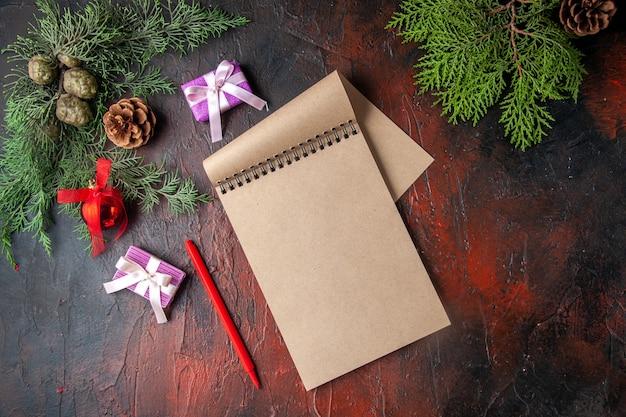 Gałęzie jodły filiżankę akcesoriów do dekoracji czarnej herbaty i prezent obok notatnika z długopisem na ciemnym tle widok poziomy