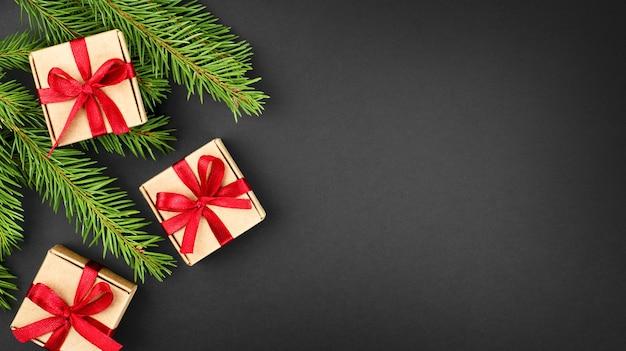 Gałęzie jodły i małe pudełka na prezenty na ciemnym tle