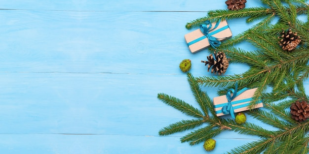 Gałęzie jodły z szyszek i prezenty na jasnoniebieskim tle.