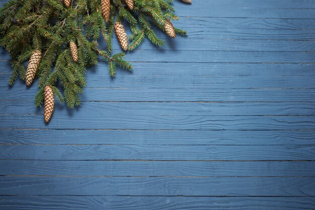 Gałęzie jodły z szyszek na niebieskim tle drewnianych