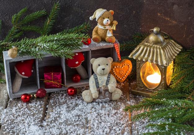 Gałęzie świerkowe, świąteczny wystrój w czerwonych kolorach, stara latarnia ze świecą i dwa zabawkowe niedźwiedzie