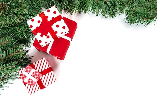 Gałęzie świerku z złote i czerwone kulki i prezenty, na białym tle. izolować.