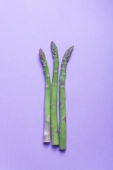 Gałęzie świeżych zielonych szparagów na liliowej powierzchni