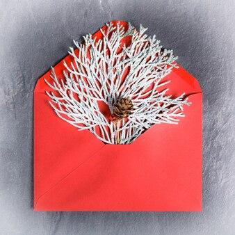 Gałęzie tui pokryte szronem w czerwonej kopercie, minimalna kartka noworoczna. płaski świeckich, widok z góry. święta, koncepcja gratulacyjna