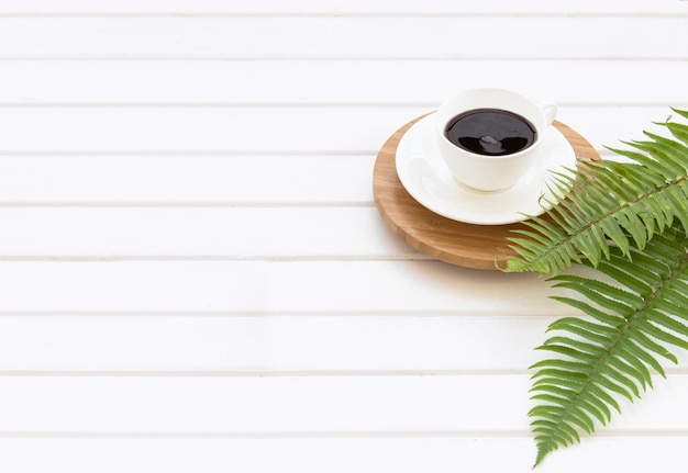 Gałęzie zielonego eukaliptusa, paproci i filiżanki czarnej kawy na tle panelu białych desek z pustym miejscem na tekst na środku