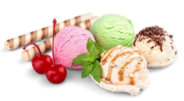 Gałki lodów z waflami i wiśniami na białym tle