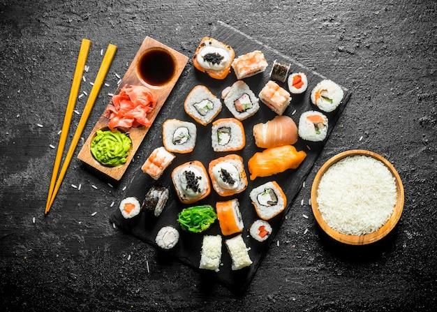 Gama różnych rodzajów sushi, bułek i maki z sosami i pałeczkami. na czarnym rustykalnym stole