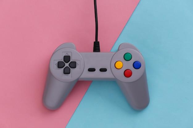 Gamepad do gier wideo. koncepcja gier retro joystick na różowym niebieskim pastelu.