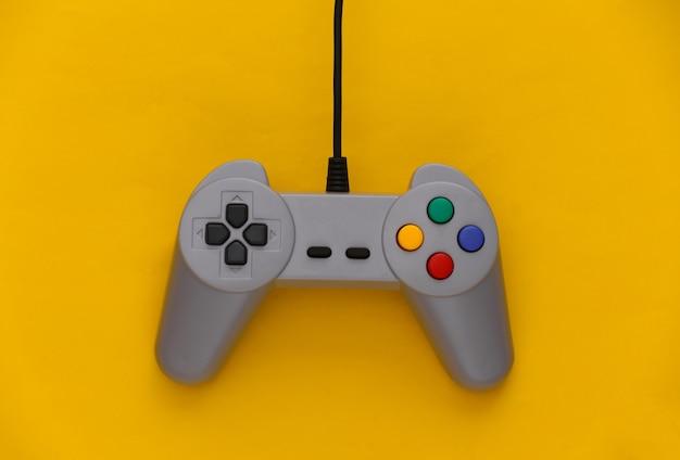 Gamepad do gier wideo. koncepcja gier retro joystick na żółto.