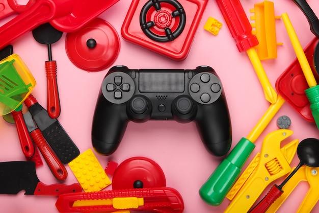 Gamepad i wiele zabawek dla dzieci na różowym pastelowym kolorze