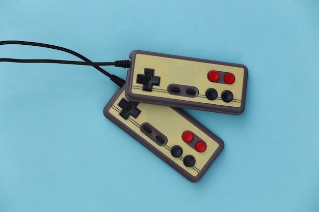Gamepady do gier wideo. koncepcja gier dwa retro joysticki na niebiesko