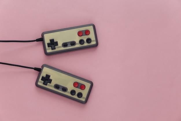 Gamepady do gier wideo. koncepcja gier dwa retro joysticki na różowo