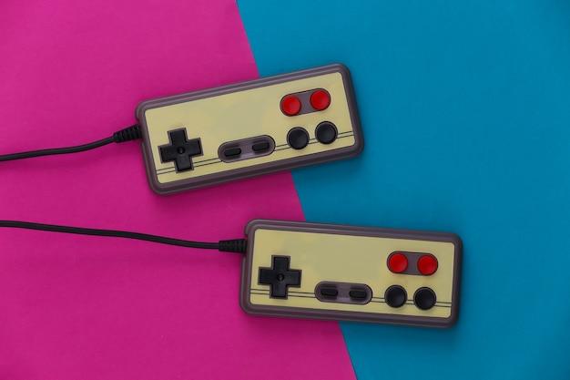 Gamepady do gier wideo. koncepcja gier dwa retro joysticki na różowym niebieskim.