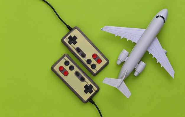 Gamepady z figurką samolotu na zielonym tle.