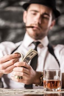 Gangster w koszuli i szelkach liczy pieniądze.