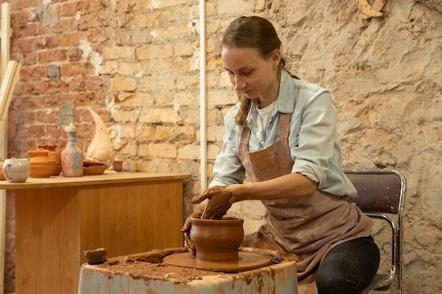 Garncarka rzeźbi gliniany garnek rzeźbiarz pracuje z gliną na kole garncarskim i przy stole