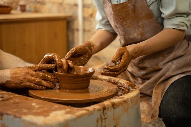 Garncarstwo szkolenie zbliżenie człowieka garncarz uczy mężczyznę, jak prawidłowo uformować miskę brązowej gliny na garncarzu
