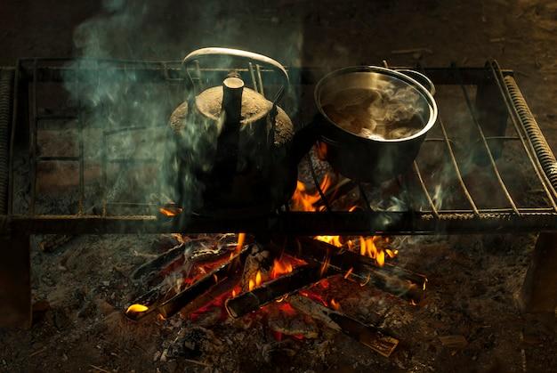 Garnek i czajnik stoją nad ogniem na przenośnym palenisku z metalowych prętów w mieszkaniu nomadów