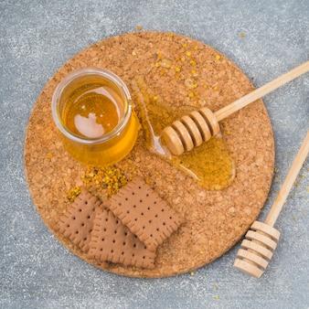 Garnek miodu; drewniana chochla; herbatniki i pyłek pszczeli na podkładce z korka