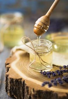 Garnek miodu, łyżka, słoik świeżego miodu, plaster miodu na drewnianym stole na zewnątrz. miód z miodową chochlą na drewnianym stole