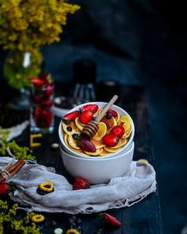 Garnek miodu na miskach owoców