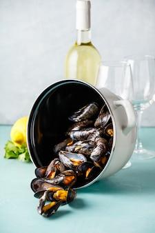 Garnek na parze małży z cytryną, ziołami i białym winem na niebieskim tle