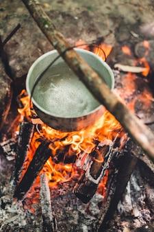 Garnek pali się nocą w pobliżu namiotu w lesie. piękne ognisko w obozie turystycznym na dziko.
