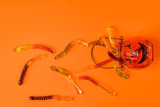 Garnek w kształcie dyni jest wypełniony robakami marmoladowymi na pomarańczowym tle koncepcji hallowee