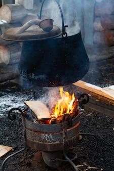 Garnek w ogniu, koncepcja dzikiego biwakowania. gotowanie w naturze podczas wędrówki.