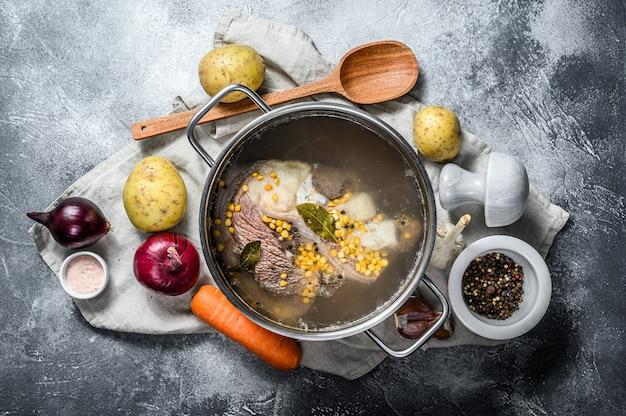 Garnek z cielęciną na kości. składniki na zupę, warzywa i przyprawy. widok z góry