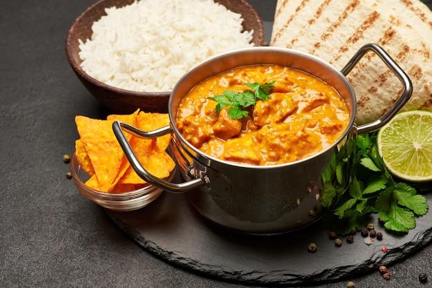 Garnek z tradycyjnym kurczakiem curry miska ryżu i pita na kamiennej desce służącej